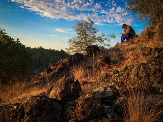 Man sitting on rocky hill at sunrise