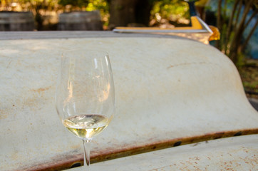 glass of white wine sitting on hood of old car