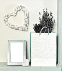 Picture frame with empty blank, lavender in paper bag and heart shape over white wall. Loft life style home decoration on vintage shelf, mockup background