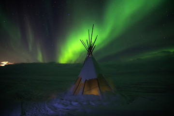 Aurora borealis lights at night in white snow tundra, Russia, North. Beautiful arctic polar landscape of green lightning  lines, clouds and moon sky with stars, nature miracle, fantastic view, wigwam
