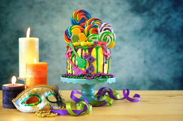 Mardi Gras theme on-trend candyland fantasy drip cake on colorful party table setting.