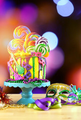 Mardi Gras theme on-trend candyland fantasy drip cake with colorful bokeh lights background.