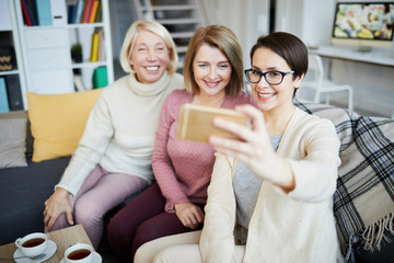 Portrait of three smiling women taking family photo via smartphone at home