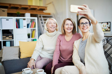 Portrait of three smiling women taking family photo via smartphone at home, copy space
