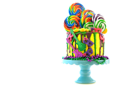 Mardi Gras theme on-trend candyland fantasy drip cake on white background.