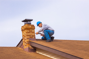Contractor Builder with blue hardhat on the roof caulking chimney