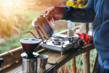 Tuinposter Kamperen close up hands drip coffee with morning light