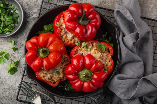 red bell peppers stuffed with meat, rice and vegetables on cast iron pan