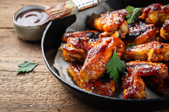 Baked chicken wings in barbecue sauce in a cast iron pan on an old wooden rustic table