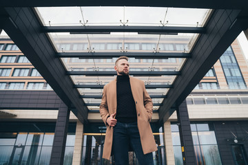 Attractive man in trendy brown coat posing near business center. Handsome european man with beard looks away. Concept lifestyle, fashionable men style