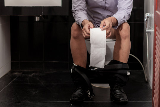 Man holding paper in toilet.
