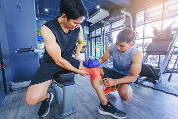Fit man with knee suffering pain has treated with hot compress by his buddy after workout at fitness gym.