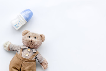 Feed baby concept. Teddy bear toy near small bottle with food on white background top view copy space