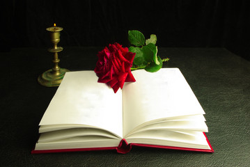 An open book, a red rose and a burning candle