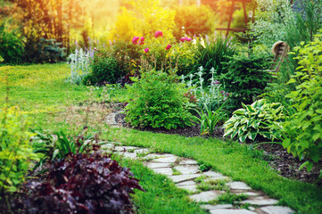 Fotobehang Tuin beautiful summer cottage garden view with stone pathway and blooming perennials