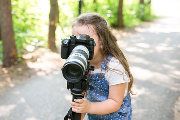 Hobby, profession, children and photographer concept - child with camera in forest