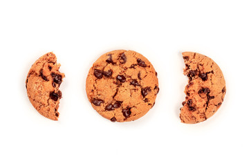 A freshly baked chocolate chip cookie and two halves of another, shot from the top on a white background with copyspace