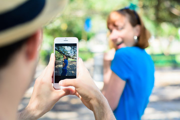 Young couple taking photo with smartphone camera.