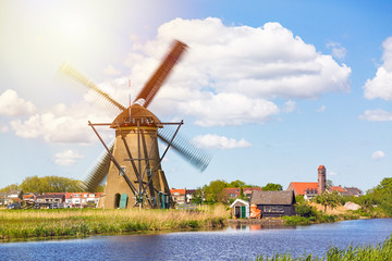 Famous windmills in Kinderdijk village in Holland. Spinning windwill. Colorful spring landscape in Netherlands, Europe. UNESCO World Heritage and famous tourist site.