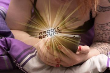 Eine junge Prostituierte mit einem Smartphone weist auf Escort Service hin