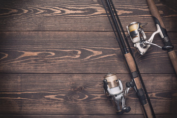 Fishing concept. Fishing spinning rods and reels with lines on wooden background with free space.