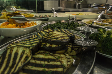 Fried eggplants, broccoli and salads in plates in the kitchen