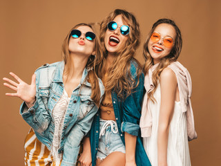 Three beautiful smiling hipster girls in trendy summer casual clothes and sunglasses. Sexy carefree women posing near golden wall. Positive models going crazy. Showing tongue Wall mural