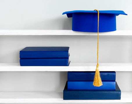 Graduation blue mortarboard on top of stack of books on wooden shelf