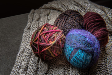 balls of yarn on a knitted blanket