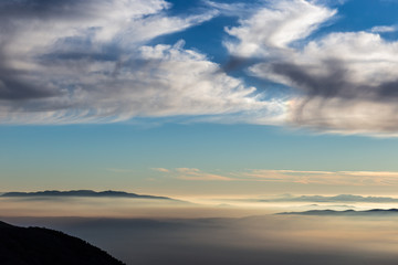 Valley filled by fog with blue sky with clouds and warm sunset colors