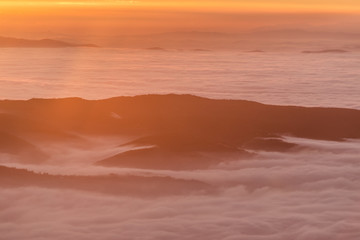 Beautiful sunset over a valley filled by fog with mountains and hills