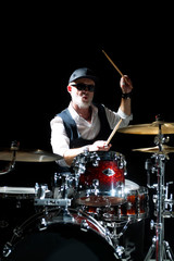 Professional drummer playing on drum set on stage on the black background