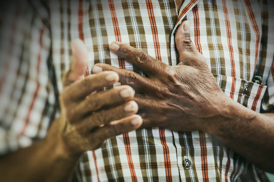 Old Asian Man Praying to Jesus Christ with His Hand on Heart in the Prayer Meeting. Vintage Color and Gain Added