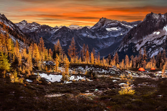 Glowing tents in mountains among snow capped peaks and golden trees.  Backcounry camping in North Cascades in autumn. Bellingham. Washington State. The United States.