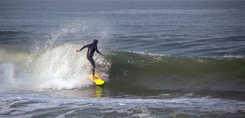 Surfer on wave at sandbar where the Santa Clara River empties into the Pacific Ocean at McGrath State Park in Ventura California United States
