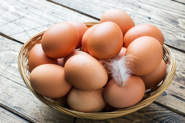 Fresh chicken eggs in the basket. Rustic wooden style background.