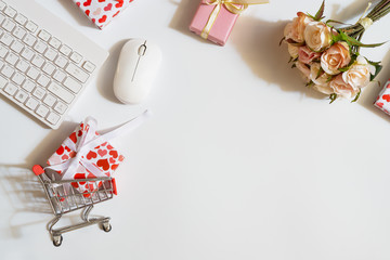 Overhead shot of wireless keyboard and mouse, gifts box with shopping cart, and rose flowers and gift box decoration. Flat lay top view office working space for Valentines shopping online concept.