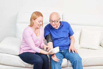 Blutdruck messen bei einem Senior zu Hause