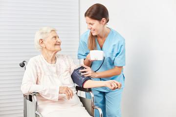 Wall Mural - Pflegekraft misst den Blutdruck einer Seniorin