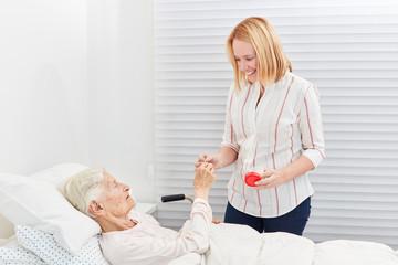 Wall Mural - Frau gibt kranker Seniorin im Bett eine Tablette