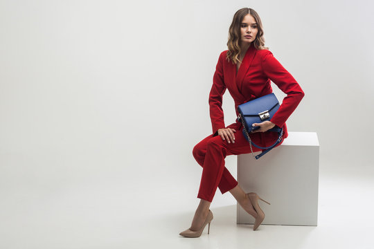 elegant woman in red suit holding blue hand bag