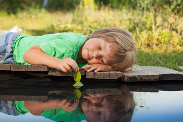 green leaf-ship in children hand in water, boy in park play with boat in river