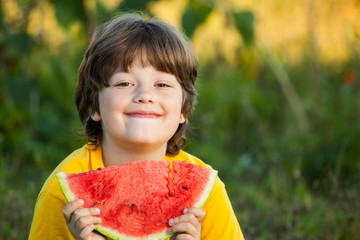Happy child eating watermelon in garden. Boy with fruit outdoors park.