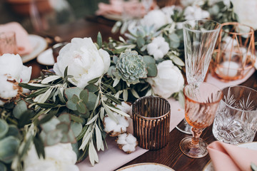 on wooden banquet table are glasses, plates, candles, table is decorated with compositions of cotton and eucalyptus branches