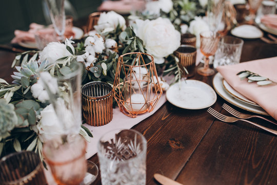 on wooden banquet table are glasses, plates, candles, table is decorated with compositions of cotton and eucalyptus branches, plates are decorated with napkins and sprig of Italian greenery