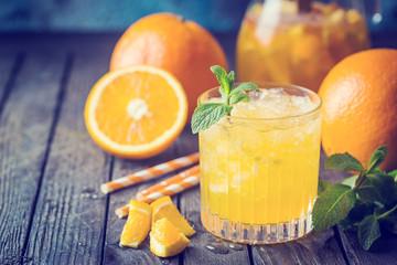Glass jar of fresh orange juice with ice and fresh fruits on dark table.