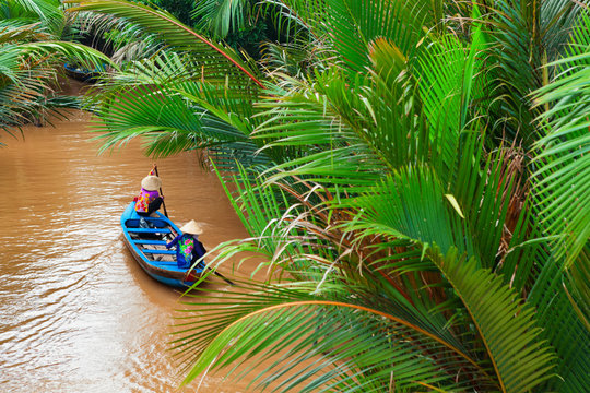 Vietnamese old women on traditional boat in Mekong river delta