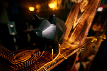 figurine of a black pig standing on a wooden shelf