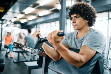Determined male working out in modern gym