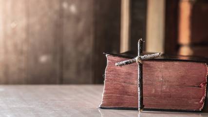 wooden cross with bible on wooden table with window light, christian concept.